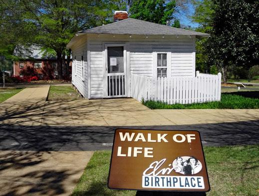 Motoglobe_Motorradreisen. Eine Hinweistafel am Boden gibt Hinweise darüber, dass im Haus im Hintergrund, Elvis geboren wurde.
