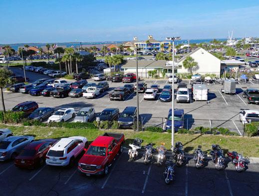 Motoglobe_Motorradreisen. Die Harley Davidson Motorräder stehen auf einem grossen Parkplatz mit vielen Autos zusammen und im Hintergrund sind mehr Autos, Parkplätze, Häuser und das Meer zu sehen.