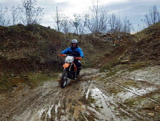 Motorradreisen: Ein Enduromaschine fährt am Sliding Kurs 2 der Cornu Master School durch eine Dreckpfütze.