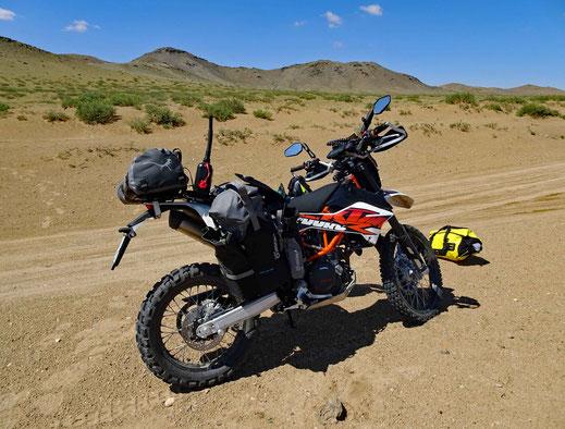 Motorrad KTM 690, gelbe Tasche, Sand, Track, grüne Büsche, blauer Himmel