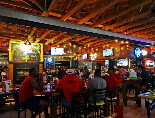 Motoglobe_Motorradreisen. Viele Leute sitzen an einem erhöhten Tisch im Restaurant  Shaggy's Pensacola Beach, USA