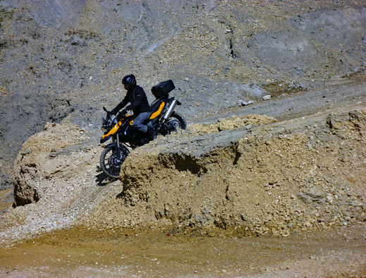Motorradreisen Motorrad fährt einen Schotterweg in der Kiesgrube herunter
