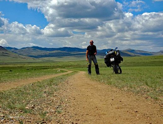 Schotterpist, grüne Wiesen, Motorrad, Mensch, Berge, bewölkter Himmel
