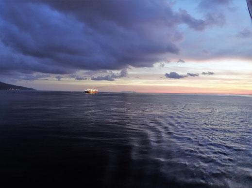 Motorradreisen auf der Schiffsfähre auf dem Meer mit dunklem Himmel