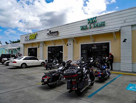 Motoglobe_Motorradreisen. Die Motorräder stehen auf einem Parkplatz vor einem Geschäfts das Wein und Spirits verkauft.