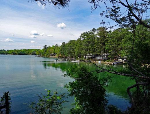 Motoglobe_Motorradreisen. Der See mit der Wasserfarbe grün, liegt vor uns und es hat viele Bäume an Ufer plus einige Häuser dazwischen.