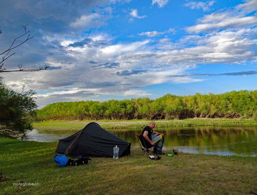 Grünes Zelt, Fluss, Wald, Mensch auf Stuhl, Wasserflasche, blauer Himmel mit weissen Wolken