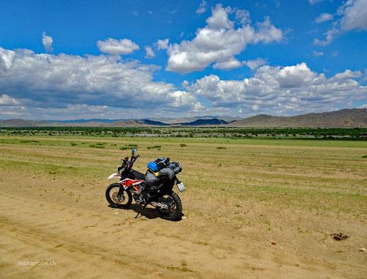 Motorrad, Sandpiste, grüne Sträucher, Fluss, blauer Himmer und weisse Wolken