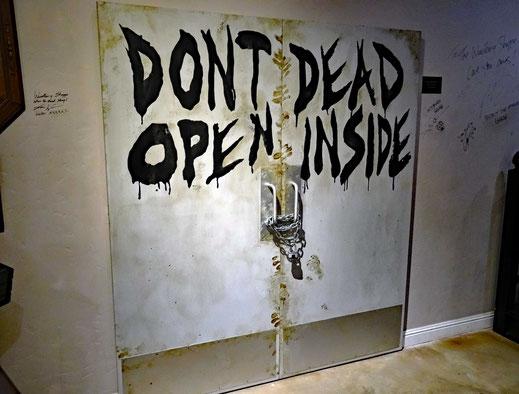 Motorglobe_Motorradreisen. Auf einer weissen Metalltüre, welche mit einer Kette und Schloss verringelt ist, steht auf Englisch geschrieben; dont dead open inside.
