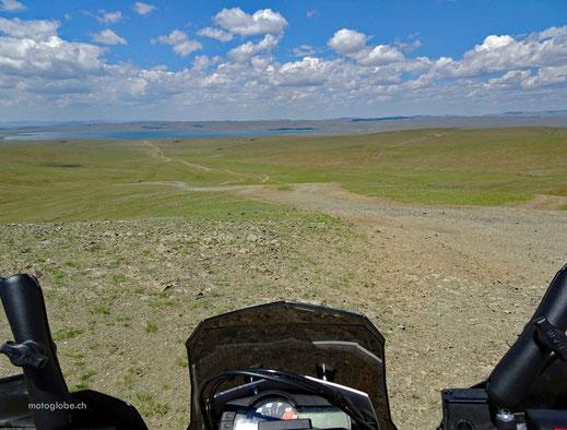 Motorradscheibe, Schotterstrasse, grüne Wiesen, See, blauer Himmel mit weissen Wolken