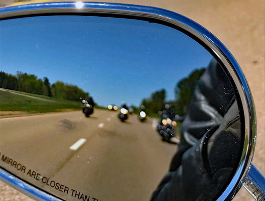 Motoglobe_Motorradreisen. Durch den Rückspiegel der Harley Davidson sieht man vier weiter Motorräder und ein Auto.