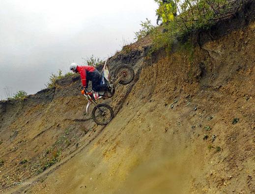 Motoglobe_Motorradreisen. Eine Enduromaschine mit einem stehenden Fahrer fahrern eine sehr steile Böschung hinunter.