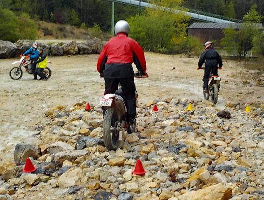 Motoglobe_Motorradreisen. Von hinten sieht man einen Enduromotorradfahrer durch eine Steinbeet in einer Kiesgrube fahren.
