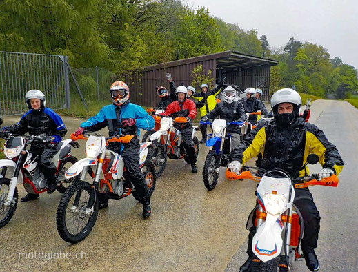 Es stehen diverse Enduromotorräder auf der Strasse und alle Fahrer haben ein Regenkombi an, weil es regnet.