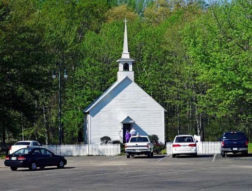 Motoglobe_Motorradreisen. Die weisse Holzkirche steht umringt von Bäumen auf einer grossen Platz, wo einige Autos geparkt sind.