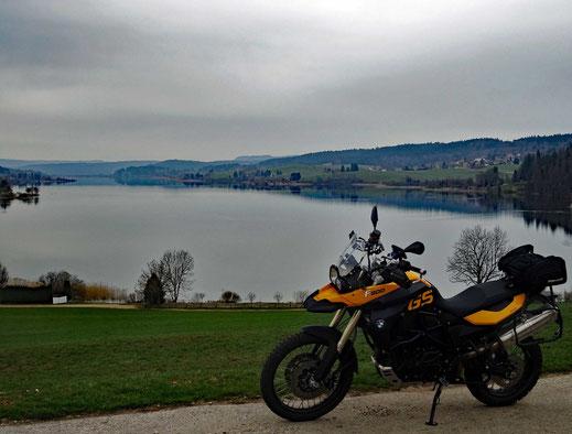 Motorradreisen: Die BMW f800GS steht auf einem Parkplatz und im Hintergrund ist der See Lac Saint-Point sehr gut sichtbar.