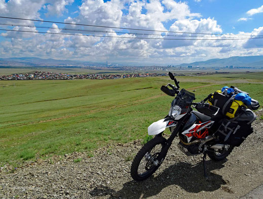 Motorrad, Teerstrasse, Häuser der Stadt Ulaanbaatar, Stromleitungen, weisse Wolken, blauer Himmel