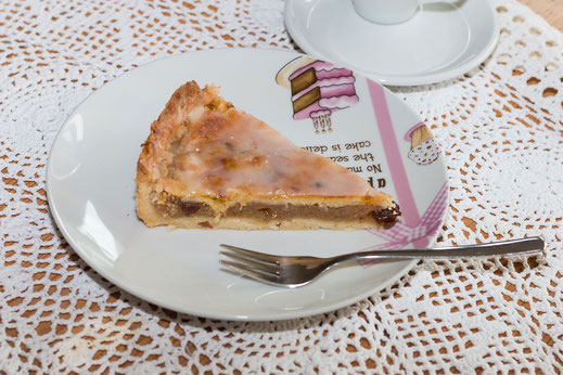 Ein Stück gedeckter Apfelkuchen auf Dessertteller mit Kuchengabel auf weisser Tischdecke