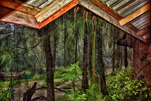 Monsunregen prasselt vom Dach eines Holzbungalows in Chaloklum Koh Phangan
