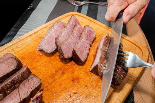 Porterhouse Steak auf einem Holzbrett in Tranchen geschnitten