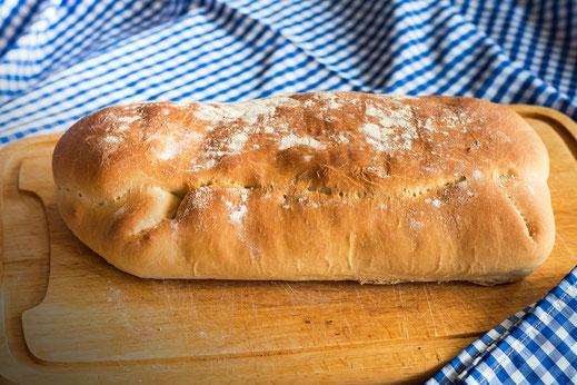Ciabatta - ganzes Brot auf Holzbrett und blau weiss karierter Tischdecke © Jutta M. Jenning