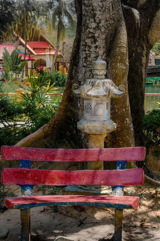 Rote Ruhebank unter Bäumen im Oriental Village auf Langkawi