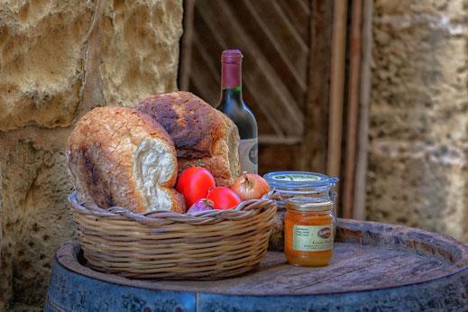 Brotkorb mit Gemüse dekoriert und einer Flasche Wein auf einem Weinfass