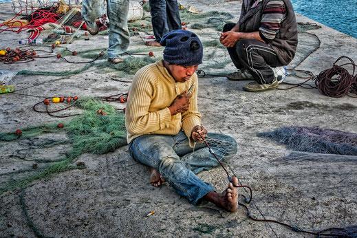 Fischer beim Netz flicken in Marsaxlokk Malta