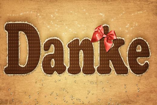 Danke-Grusskarte mit Schokoladenschrift und roter Schleife auf braunem Hintergrund