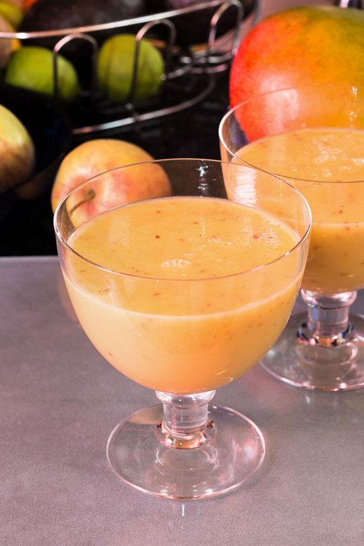 Zwei Glasschalen Fruchtsmoothie mit Avocado. Im Hintergrund Früchte
