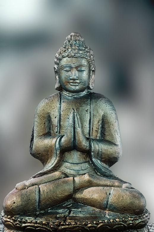 Sitzender betender Buddha, gold-und silberfarben vor grau-grünem weichen Hintergrund © Jutta M. Jenning www.mjpics.de