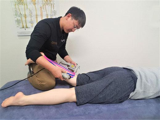 テーピング療法の施術中です。特殊な機器も使用します。