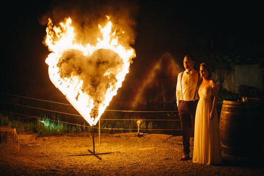 Braut und Bräutigam stehen bei ihrer Feuershow zur Hochzeit neben einem Feuerherz