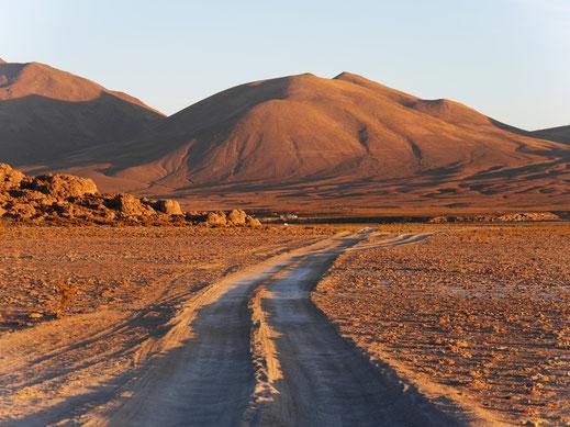 Ein grauer und langweiliger Berg wird im Sonnenuntergang ein Spektakel in Orange, am Rande des Salar de Uyuni, Bolivien (Foto Jörg Schwarz)