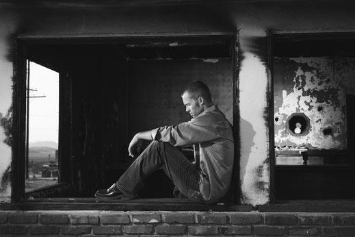Junger Mann weinend sitzend depressiv traurig
