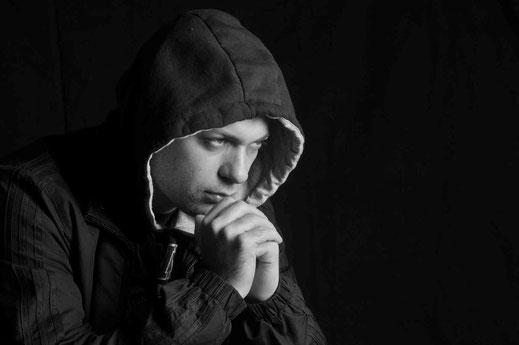 Junger Mann sitzend böse depressiv aggressiv