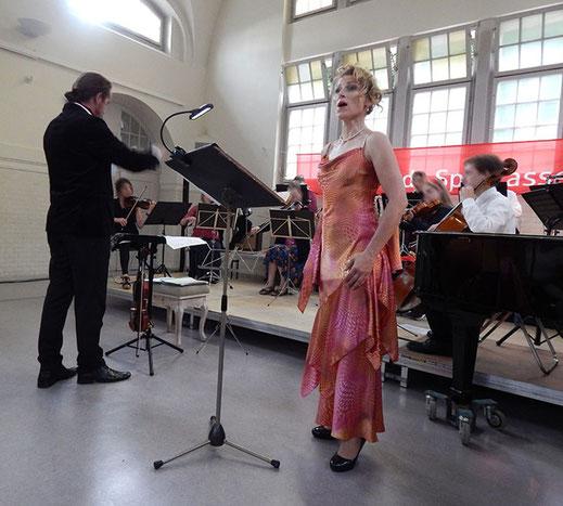 Dirigent Shenoll Tokaj mit Sängerin und Orchester