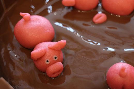 Schlamm-Kuchen mit schwimmenden Schweinchen aus Marzipan