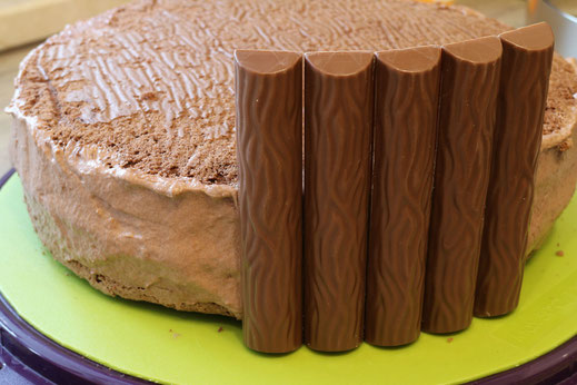 assembly of chocolate bars on cake