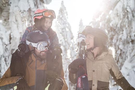 Erwachsener Skiläufer und Kind schauen auf die Piste hinunter