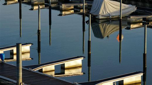 Pfähle im Hafen beim Weissen Haus in Altenrhein spiegeln sich im Wasser.