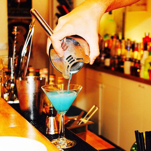 Blue Lady wird in ein Cocktailglas abgeseiht im Barkurs