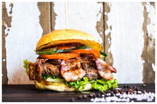 LUCKY LUKE Burger - Der krosse Cowboy - Rindfleisch, gebr. Speck, karamellisierte Zwiebeln, Salat, Tomate, Gurken, Heinz BBQ & Heinz Ketchup
