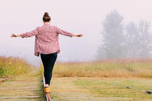 Jeune fille en équilibre sur des rails