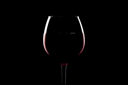 Weinglas mit Rotwein unter minimalistischer Beleuchtung mit Kantenlicht und schwarzem Hintergrund von Tobias Gawrisch (Xplor Creativity)