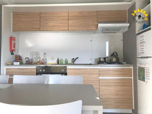 Die Küche des Mobilheims Azure von Eurocamp mit großem Esstisch.