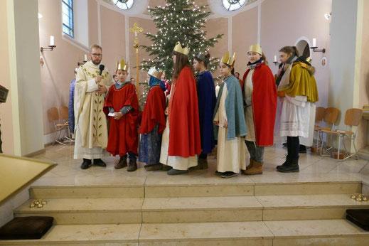 Sieben Sternsinger tragen die Fürbitten vor