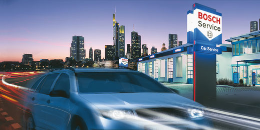 Ein Auto fährt an einer BOSCH Service Werkstatt vorbei. Es ist abends und im Hintergrund ist die Skyline einer Stadt zu sehen. / Bildquelle: BOSCH Service