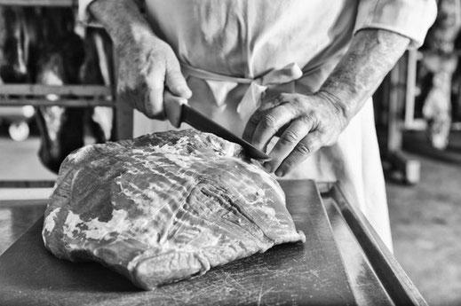 Bild: Hans Hügle beim schneiden von Fleisch