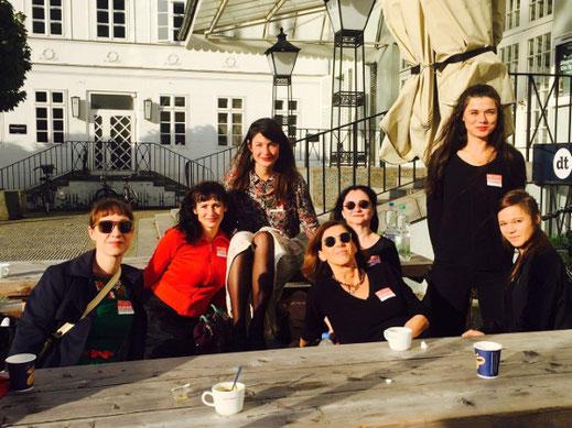 Die Gründerinnen sitzen an einem langen Biertisch im Innenhof des Deutschen Theaters in Berlin, sie tragen Sonnenbrillen und Namensschilder, vor ihnen stehen Kaffeetassen.